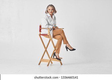 An elderly woman sits on a high chair in a white shirt Gray isolated background
