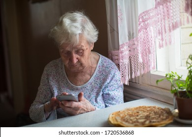 Elderly woman sits with a smartphone in her hands at home.