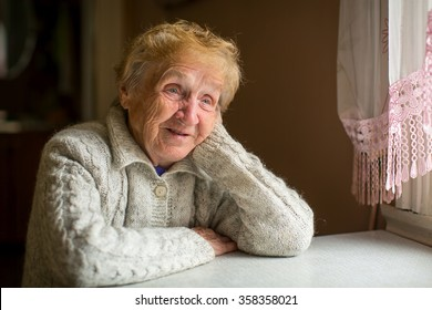 An elderly woman sits at a table near the window.