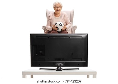 Elderly woman sitting in an armchair and watching football on television isolated on white background