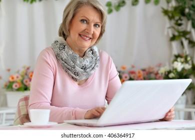 ältere Frau, die mit einer Tasse am Computer sitzt