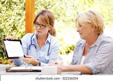Elderly woman sitting in the garden with home health care nurse and consulting. Middle age caregiver holding in hand digital tablet with blank screen and giving advice to her patient.