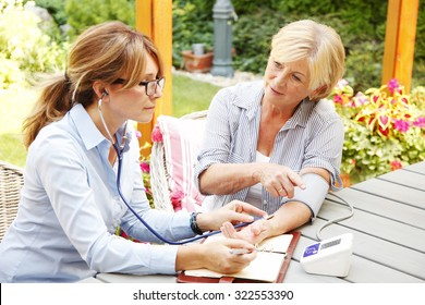 Elderly woman sitting in the garden with home health care nurse an using blood pressure. Home caregiver female consulting with her patient.