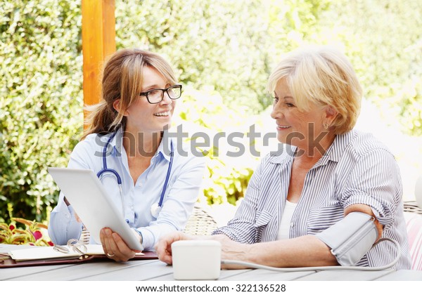 Ältere Frau sitzt im Garten mit Heim Krankenschwester und Beratung. Pflegepersonal im Mittelalter, das digitale Tablette in der Hand hält und ihre Patientin berät.