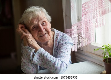 Elderly woman sitting in her home.