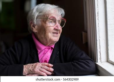 An elderly woman sitting in the house near the window.