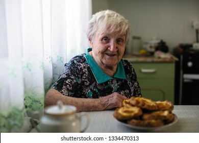Elderly woman sitting in the kitchen.