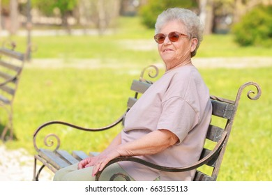 Elderly woman sitting on bench in park