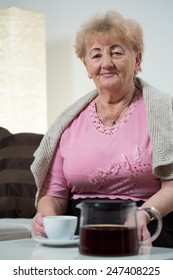 Elderly woman sitting on sofa and drinking coffee