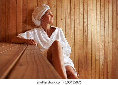 Elderly woman sitting relaxed in a wooden sauna