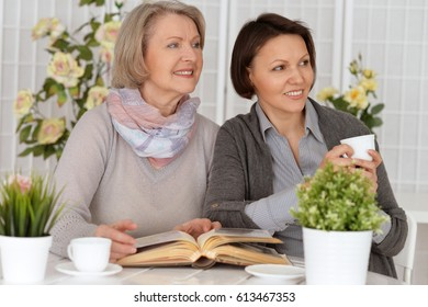 elderly woman sitting at the table with her daughter and reading a book