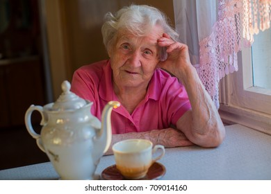 An elderly woman sitting at a table with a kettle and a cup of tea.