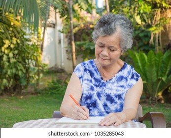Elderly woman sitting writing a book at the table in the garden