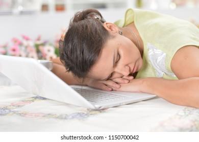 Elderly woman sleeping near  laptop