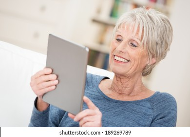 Elderly woman smiling happily as she reads the screen on her tablet computer checking on her social networking contacts
