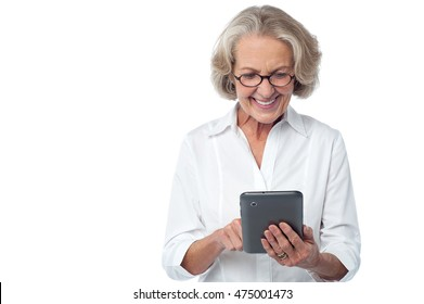 Elderly woman smiling happily as she reads the screen on her tablet