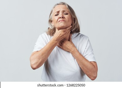 Elderly woman with sore throat sore throat holding her neck in a white t-shirt