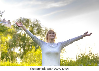 Elderly woman stands with one hand open in a sunny park. How to be happy and active in old age