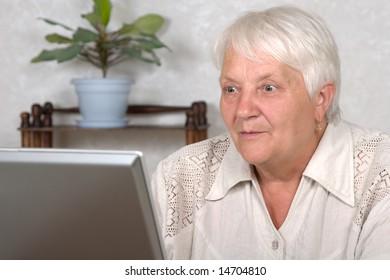 The elderly woman studies the computer