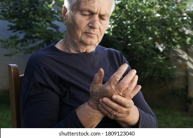 Elderly woman suffering from hand pain. Arthritis symptoms.