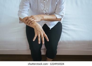 Elderly woman suffering hand with parkinson's disease symptoms