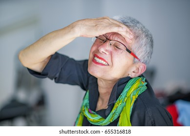 Elderly woman suffering from headache at home