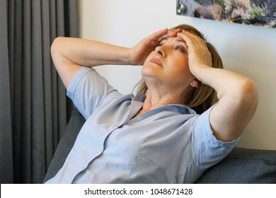 Elderly woman suffering from headache migraine pain at home. Health problem, stress and depression. Female holds head with hand. Concept of health.