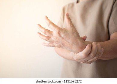 Elderly woman suffering from pain, weakness and tingling in wrist. Causes of hurt include osteoarthritis, rheumatoid arthritis, gout or wrist sprain. Health care concept. Copy space.