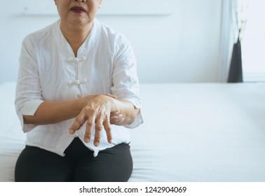 Elderly woman suffering with parkinson's disease symptoms on hand