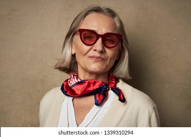Elderly woman in sunglasses and a bright scarf around her neck on a brown background