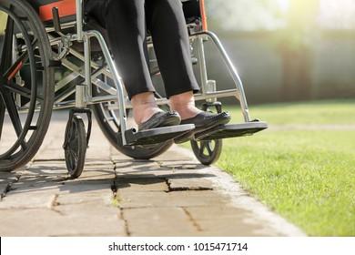 Elderly woman swollen feet on wheelchair in backyard