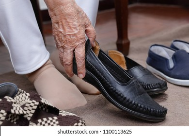 Elderly woman swollen feet putting on shoes at home.