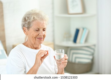 Elderly woman taking medicine at home