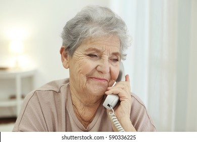 Elderly woman talking by telephone at home