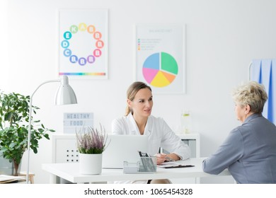 Elderly woman talking to a female doctor at a diet consultation in a bright office
