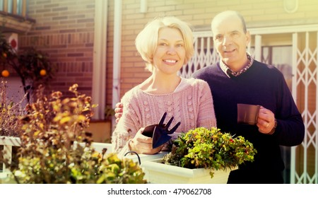 Elderly woman talking with male neighbor at balcon