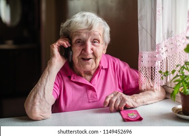 An elderly woman talking on the phone sitting at the table.