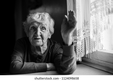 An elderly woman talking sitting at the table. Black and white.