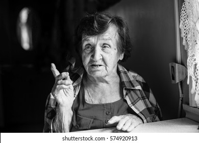 Elderly woman talking sitting at the table. Black-and-white photo.