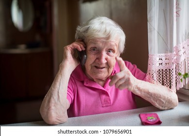 An elderly woman talks emotionally on a mobile phone.
