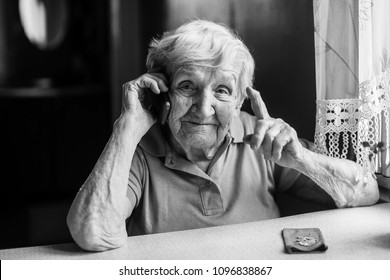 Elderly woman talks on a mobile phone.