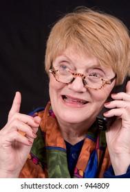 An elderly woman talks on the phone