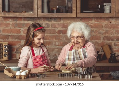 Elderly woman teaching a little girl to bake cookies