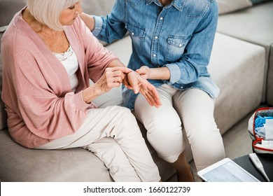 Elderly woman telling family physician about injured arm stock photo