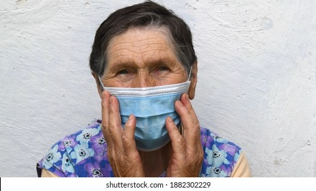 Elderly woman touches single-use mask with both hands. Portrait of old lady with deep wrinkles on her forehead and near eyes. Aged wrinkled face of 80 year old woman