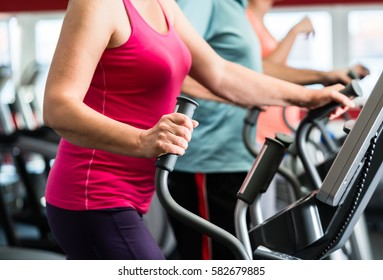 Elderly woman training on cross trainer at the gym