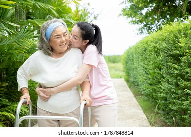 An elderly woman try to patient exercise by walker in the garden because she was sick with heart disease and high blood pressure. She needs to have someone closely supervised to prevent accidents.