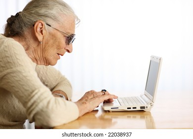 Elderly woman typing on ultra portable laptop computer. Shallow DOF.