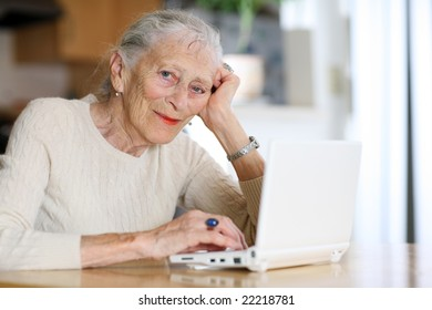 Elderly woman typing on ultra portable laptop computer. Shallow DOF.