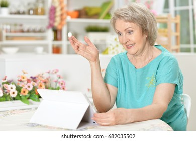An elderly woman uses a tablet